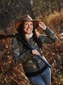 stock photo of shotgun  - Waterfowl hunting the female hunter carry a shotgun autumnal bushes on background - JPG