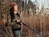 picture of shotgun  - Waterfowl hunting the female hunter loading the side by side shotgun shore and reeds on background - JPG