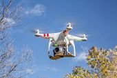 FORT COLLINS, CO, USA, November 1, 2014:  Airborne radio controlled Phantom 2 quadcopter drone flying over trees with  the Panasonic Lumix GM1 camera mounted on a home made platform.