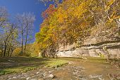 Fall Colors And A Limestone Cliff Over A Quiet Stream.