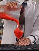 Barman preparing strawberry daiquiri cocktail.