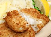 Breaded haddock fish fillets served with mash and peas.