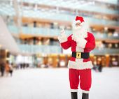 christmas, holidays, gesture and people concept - man in costume of santa claus pointing fingers over shopping center background