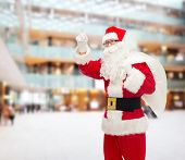 christmas, holidays, gesture and people concept - man in costume of santa claus with bag pointing finger up over shopping center background
