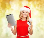 christmas, technology, shopping and people concept - smiling woman in santa helper hat with tablet pc computer and credit card over yellow lights background