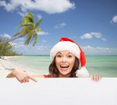 christmas, x-mas, people, advertisement and sale concept - happy woman in santa helper hat with blank white board over tropical beach background
