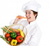 Happy female chef holding a basket of fresh, organic, locally grown produce and eating a raw carrot.  Isolated on white background.