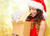 christmas, holidays, celebration and people concept - smiling woman in red dress with gift box over yellow lights background