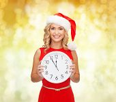 christmas, winter, holidays, time and people concept - smiling woman in santa helper hat and red dress with clock over yellow lights background