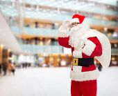 christmas, holidays and people concept - man in costume of santa claus with bag looking far away over shopping center background