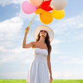 happiness, summer, holidays and people concept - smiling young woman wearing sunglasses with balloons over blue sky and grass background