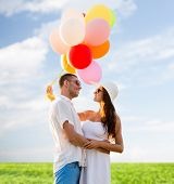 love, wedding, summer, dating and people concept - smiling couple wearing sunglasses with balloons hugging over blue sky and grass background