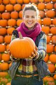 Closeup On Smiling Young Woman Holding Pumpkin