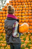 Young Woman Holding Pumpkin In Front Of Pumpkin Rows. Rear View