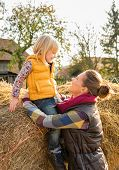 Happy Mother And Child Sitting On Haystack