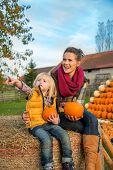 Happy Mother And Child Sitting On Haystack With Pumpkins And Poi