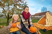 Happy Mother And Child Sitting On Haystack With Pumpkins