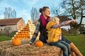 Mother And Child Sitting On Haystack With Pumpkins And Pointing