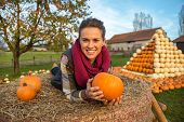 Portrait Of Smiling Young Woman Laying On Haystack With Pumpkins