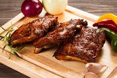 Barbecued ribs with vegetables on cutting board