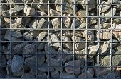 Wall of steel and stones in sunlight