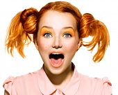 Screaming Funny Teen model Girl face closeup. Beauty funny teenage girl with open mouth looking at camera. Surprised woman. Red hair