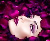 High Fashion Vogue style model portrait with rose petals. Fashion art glamour Woman portrait with bright violet make-up and flowers petals round face. Holiday makeup