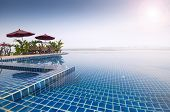 picture of infinity pool  - The edge of an infinity swimming pool at a tropical hotel on the edge of a river  - JPG