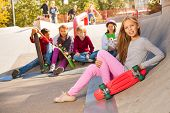 Girl with skateboard and friends sitting behind