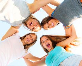 stock photo of huddle  - Group of Four Teenage Girls having fun outdoors - JPG