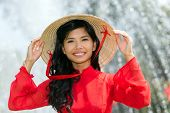 picture of vivacious  - Smiling vivacious Vietnamese woman in a traditional red outfit and conical hat standing in front of a fountain smiling at the camera - JPG