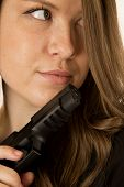 picture of pistols  - Female model glancing sideways holding black pistol - JPG