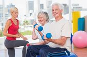 picture of senior class  - Portrait of happy senior couple lifting dumbbells while instructor guiding them in gym - JPG