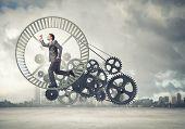 foto of hamster  - Young businessman in suit running in hamster wheel - JPG