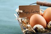 image of bird egg  - Bird eggs in wicker basket with decorative flowers on color wooden background - JPG