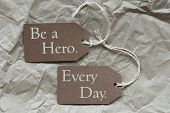 stock photo of incredible  - Two Brown Labels Or Tags With White Ribbon On Crumpled Paper Background With English Life Quote Be A Hero Every Day Vintage Or Retro Style - JPG