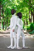 foto of rapier  - Two rapier fencers women staying in park alley getting ready for competition - JPG
