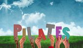 pic of pilates  - Hands holding up pilates against blue sky over green field - JPG