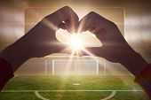 stock photo of football pitch  - Woman making heart shape with hands against football pitch with goalpost and scoreboard - JPG