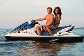 picture of ski boat  - Multi ethnic couple sitting on a jet ski - JPG