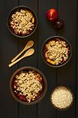 stock photo of crisps  - Overhead shot of rustic bowls filled with baked plum and nectarine crumble or crisp photographed on dark wood with natural light - JPG