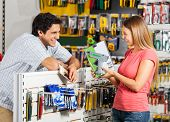 stock photo of hardware  - Playful couple with cordless drill in hardware store - JPG