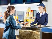 stock photo of popcorn  - Mid adult pregnant woman buying popcorn from seller at cinema concession stand - JPG