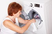 foto of stereotype  - Woman puts clothes in the washing machine at home - JPG