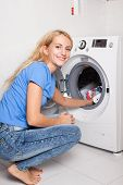 pic of stereotype  - Woman puts clothes in the washing machine at home - JPG