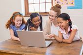 image of pupils  - Teacher and pupils looking at laptop at the elementary school - JPG