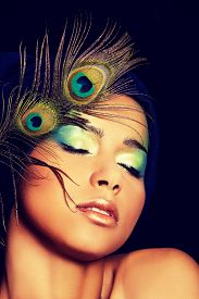 stock photo of female peacock  - Beauty woman with artistic make up and peacock feather - JPG