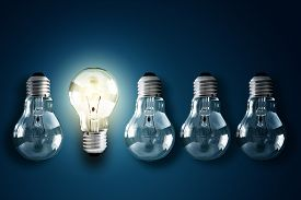 stock photo of illuminated  - Illuminated light bulb in a row of dim ones concept for creativity - JPG