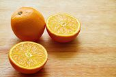 stock photo of orange  - Orange and two halves of orange on the wooden table - JPG