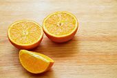 picture of orange  - Two halves of orange and orange lobule on the wooden table - JPG